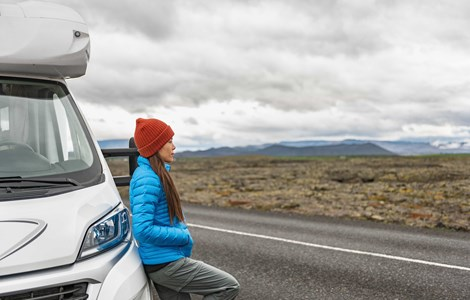 Woman in red hat and blue coat leaning on campervan