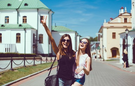 Two girls laughing and posing for selfie on holiday in front of idyllic buildings and river