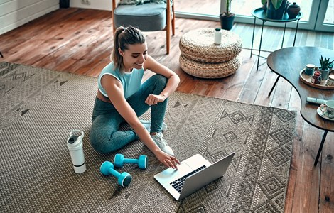 Lady doing workout on floor at home on laptop