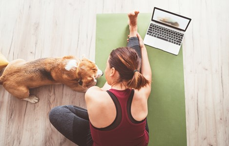 Woman doing yoga on floor with laptop and dog beside her