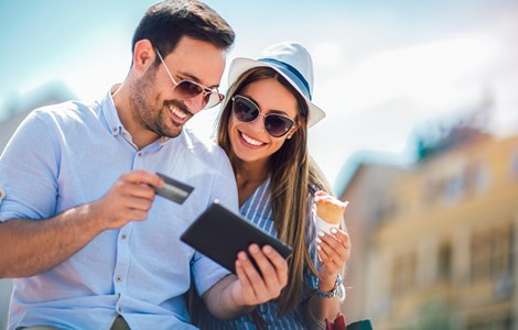 Couple sat with card and tablet in the sun eating ice cream